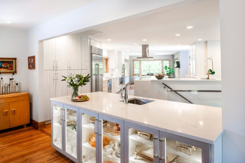 Beautiful Rock Star transitional bright Tulsa kitchen with glass front lit island storage, wood floors and professional stainless appliances