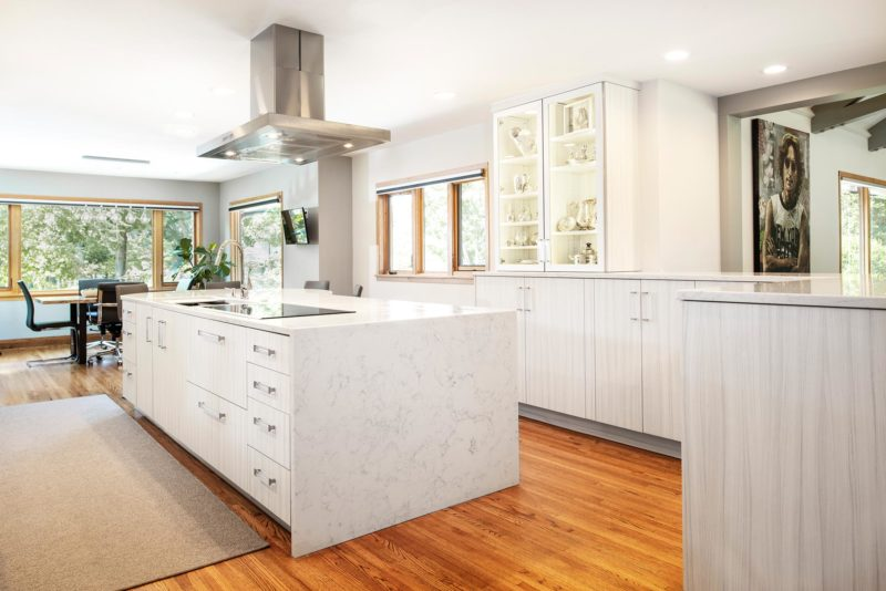 Beautiful Rock Star transitional bright Tulsa kitchen with stainless professional hood over island and induction cooktop