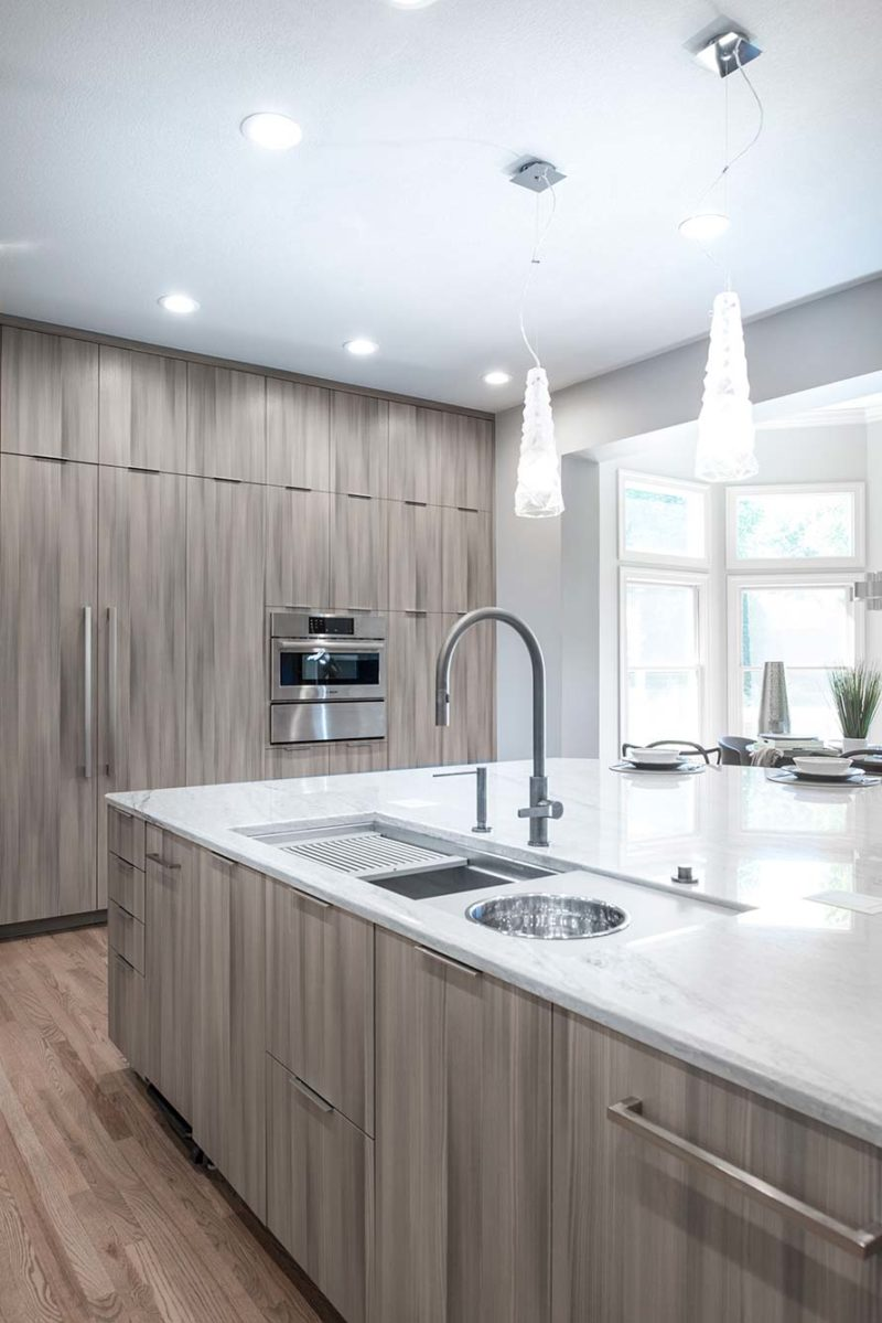 Culinary Elegance 5 warm transitional open kitchen with large island featuring Galley Workstation stainless kitchen sink and beautiful Harmoni cabinet storage