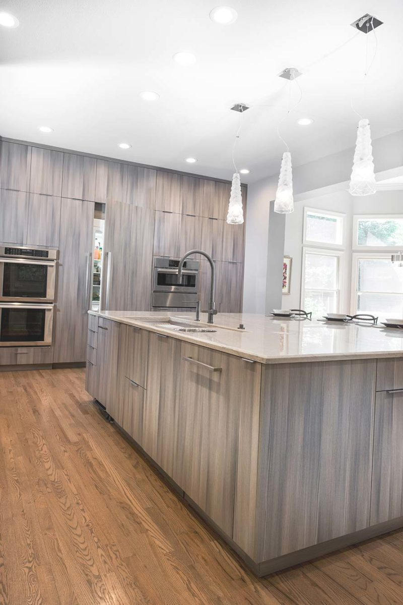 Culinary Elegance 6 warm transitional open kitchen with large island featuring Galley Workstation stainless kitchen sink, beautiful Harmoni base cabinet storage and integrated refrigerator and freezer