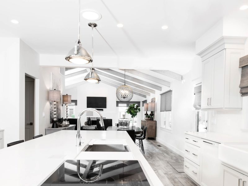 Anything But Vanilla 6 classy modern kitchen with Galley Workstation stainless steel kitchen sink and induction cooktop open to the living room