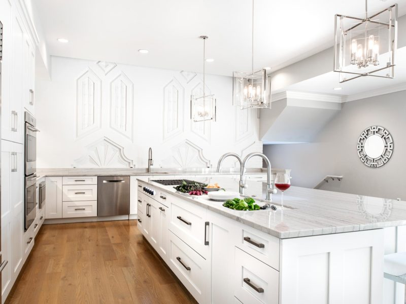 Art deco white Tulsa penthouse kitchen remodel with Galley Workstation and transitional gas cooktop on the large island including base storage and wood flooring