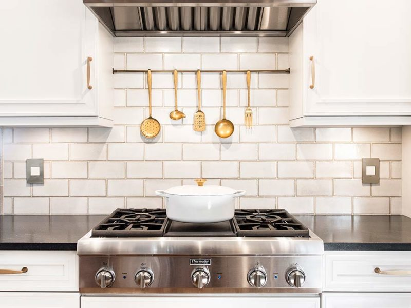 Traditional Tulsa kitchen including stainless Thermador gas rangetop and vent hood accented by white subway tile backsplash.