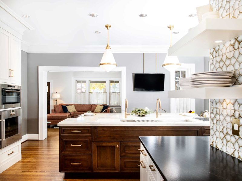 Beautiful remodeled and designed Tulsa kitchen with Galley Workstation large kitchen sink in the island featuring red birch cabinet storage and honed white marble counter tops