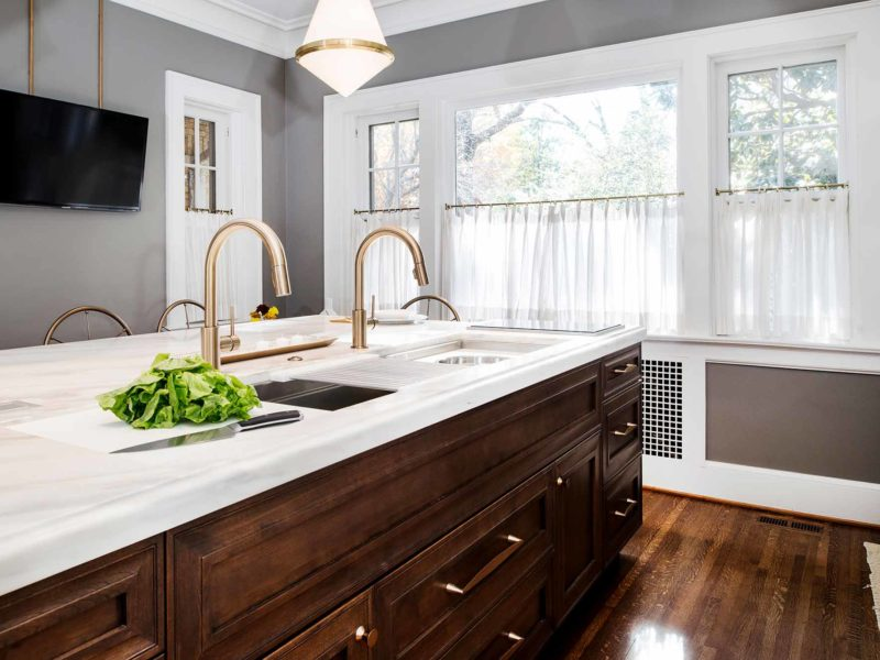 Beautiful Tulsa kitchen remodeled and designed with a Galley Workstation large kitchen sink and large island with red birch cabinet storage, white marble counter top and induction cooking