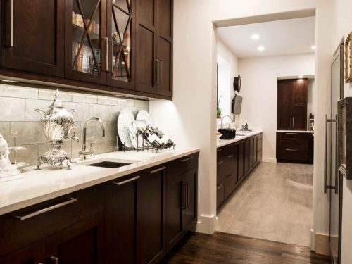 Walk-in bar space with bar sink, rich brown cabinetry, tile backsplash, quartz counter top open to Tulsa homeowner kitchen remodel