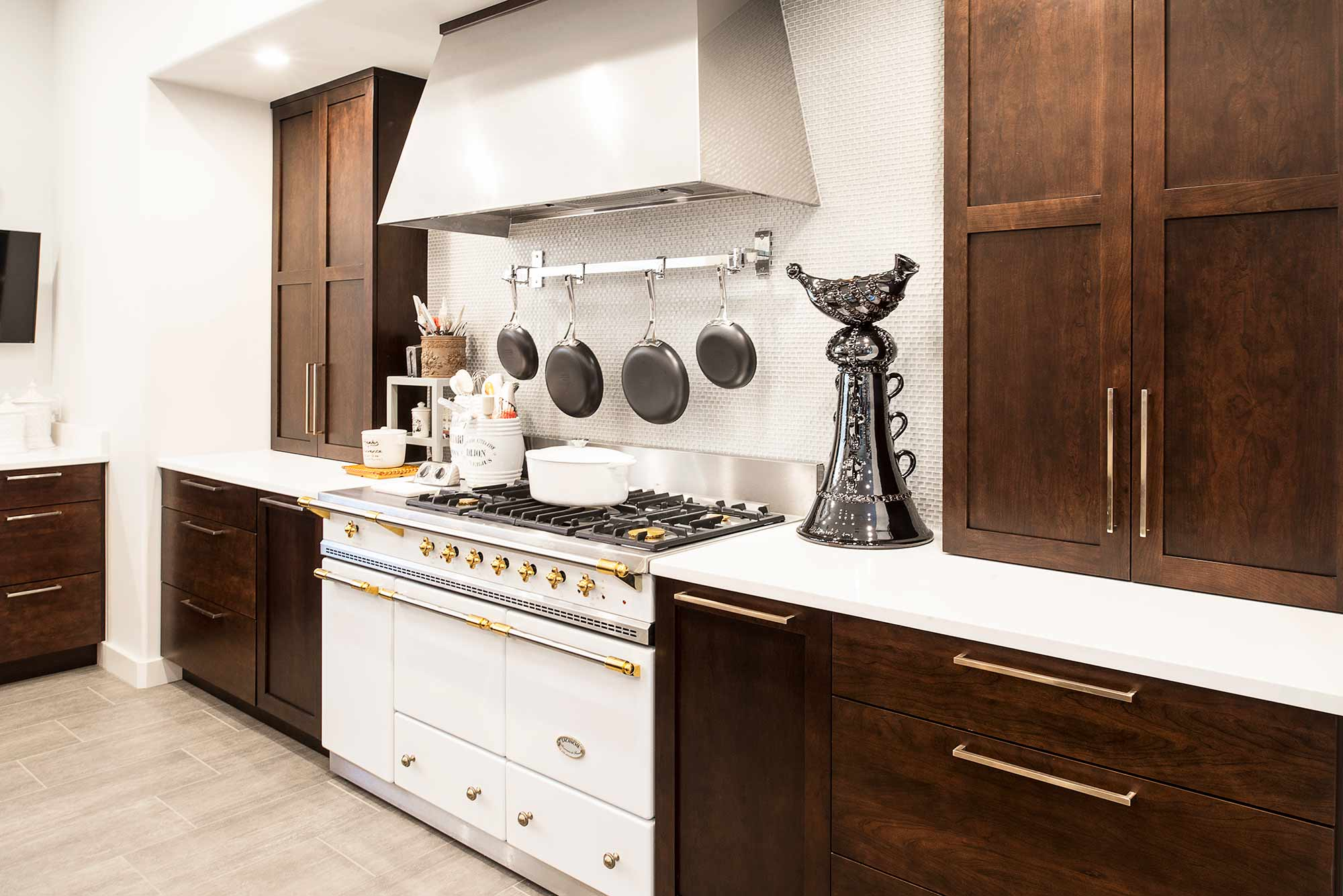 Lacanche french gas range in Tulsa kitchen remodel with vent hood rich brown cabinet storage, ceramic tile backsplash and quartz counter-top