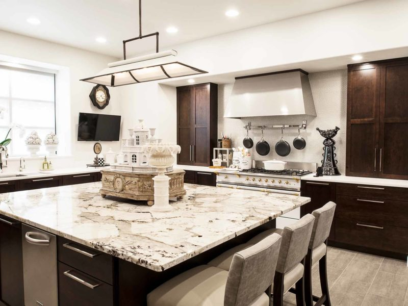 Classy Tulsa kitchen remodel with marble counter-tops, island seating, rich brown base cabinet storage, decorative pendant lighting and Lacanche french range