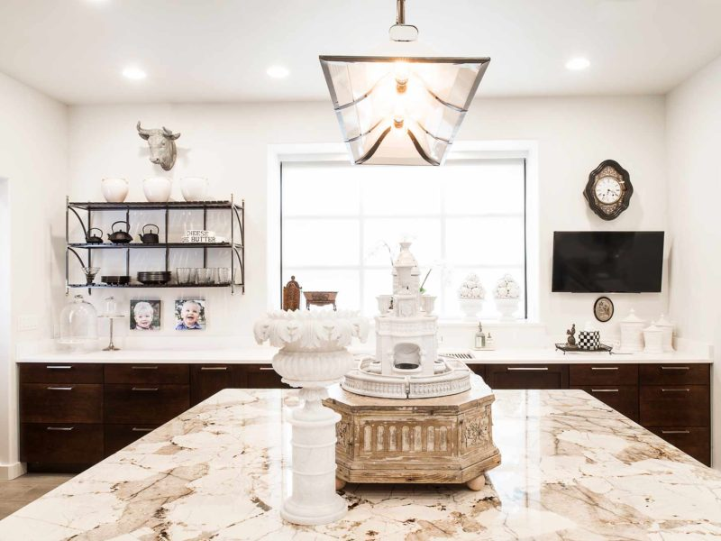Classy Tulsa kitchen remodel with marble counter-tops, rich brown base cabinet storage, island with decorative pendant lighting and open shelves