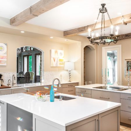 Comfy Tulsa kitchen remodel with tile floors, two islands including a beverage refrigerator, induction cooktop, coffee and beverage space, aged wood ceiling beams and rustic chandelier