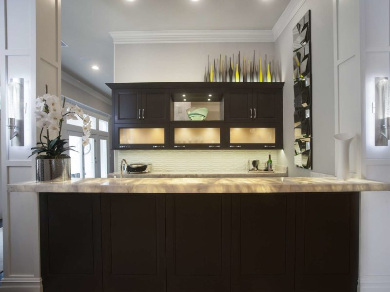 Contemporary designed and remodeled Tulsa open bar area, lit frosted glass wall cabinets, dark brown cabinet storage, glass tile backsplash and granite counters