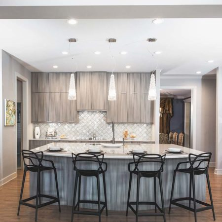 Elegant contemporary open Tulsa kitchen, large island, Galley Workstation, rich brown Harmoni cabinets, refinished wood floors, Bosch stainless appliances and decorative pendant lights