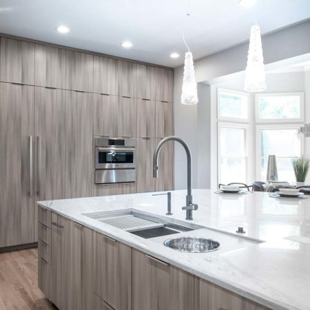 Elegant contemporary open Tulsa kitchen designed with large island, Galley Workstation kitchen sink, Harmoni cabinet island storage, quartz countertops and decorative pendant lights