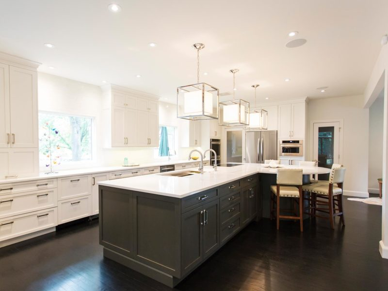 Elegant Tulsa kitchen design with large island, stained cabinets, quartz counters, white cabinets, vinyl floors, decorative pendant lights and Galley Workstation with induction cooktop