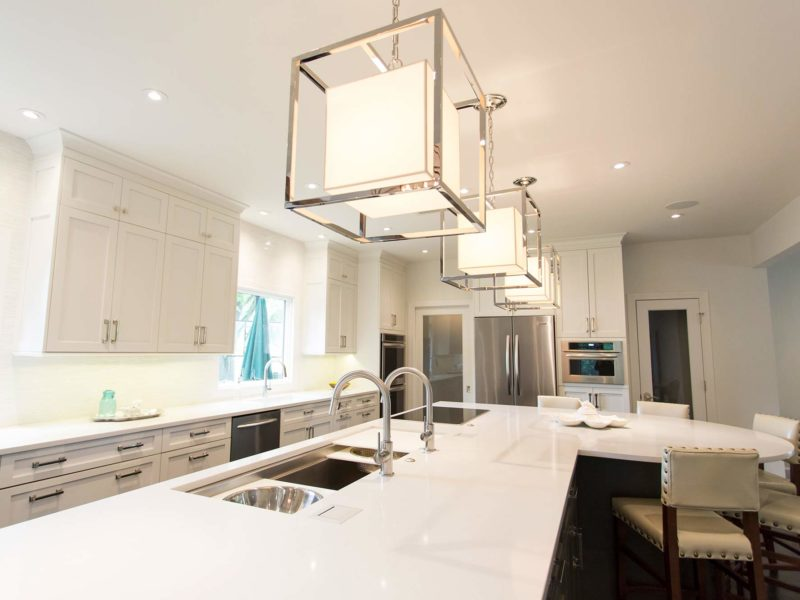 Open Tulsa kitchen design and remodel with Galley Workstation large kitchen sink and induction cooktop in the large island and seating, white cabinets, quartz counters and island pendant lights