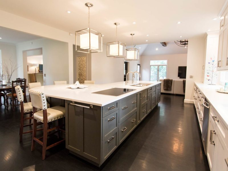 Open Tulsa kitchen remodel and design featuring a large island with stained cabinets, quartz counter top, white cabinets, vinyl flooring, decorative island pendant lights and induction cooktop