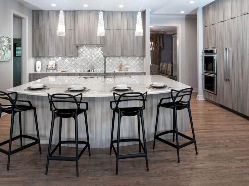 Elegant warm contemporary open Tulsa kitchen remodel with large island, decorative pendant lights, Galley Workstation, beautiful Harmoni cabinets, quartz counters, decorative backsplash, refinished wood floors and stainless Bosch appliances