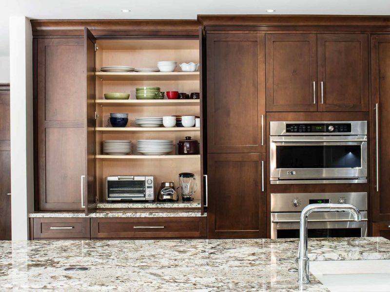 Handsome rich Tulsa kitchen remodel with tall shelf storage, coffee center, GE Monogram microwave and oven and dark brown cabinetry