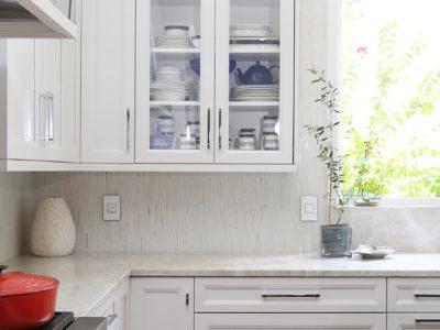 Modern kitchen remodel kitchen and bath Tulsa remodel decorative hood, Wolf professional gas range, tile backsplash and glass insert wall cabinet storage