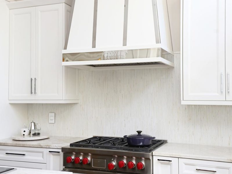 Kitchen and bath ideas Tulsa modern kitchen remodel with decorative vent hood, Wolf professional gas range, tile backsplash and white cabinets wall storage