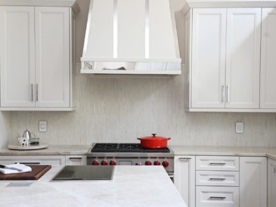 Kitchen concepts Tulsa modern kitchen remodel with decorative hood, Wolf professional gas range, tile backsplash, kitchen island induction cooktop