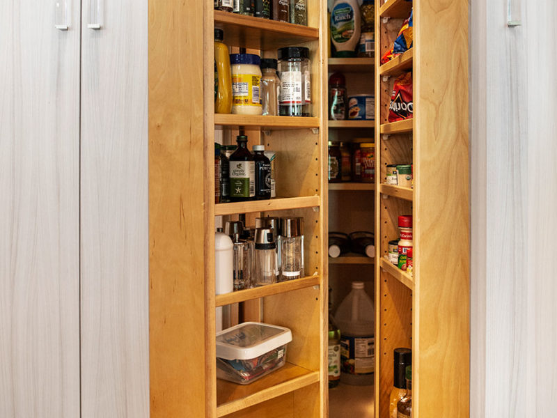 Large open transitional white Tulsa kitchen remodel with tall pantry storage with clear cabinet hardware for storing condiments and dry food goods and wood flooring