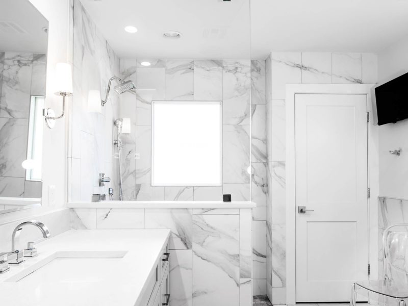 Modern fresh white Tulsa master bathroom with vanity walk-in shower, glass partition, tile walls and wall mounted television