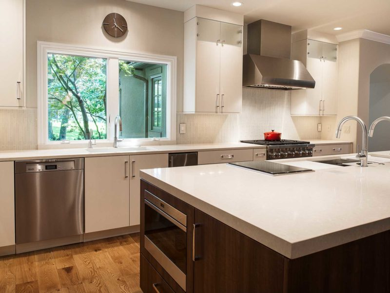 Modern functional large Tulsa kitchen with quartz counter-tops, white cabinets, stainless dishwasher, large island, drawer microwave, Wolf induction cooktop and Galley Workstation