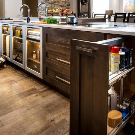 Modern south Tulsa kitchen island with pull-out base pantry brown cabinet storage and luxury vinyl wood flooring