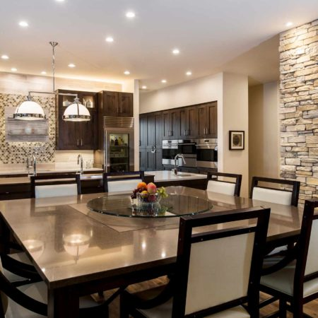 Modern south Tulsa kitchen with pull-out wood table, Caesarstone counters, decorative island pendant lights, large island, stone wall and luxury vinyl flooring