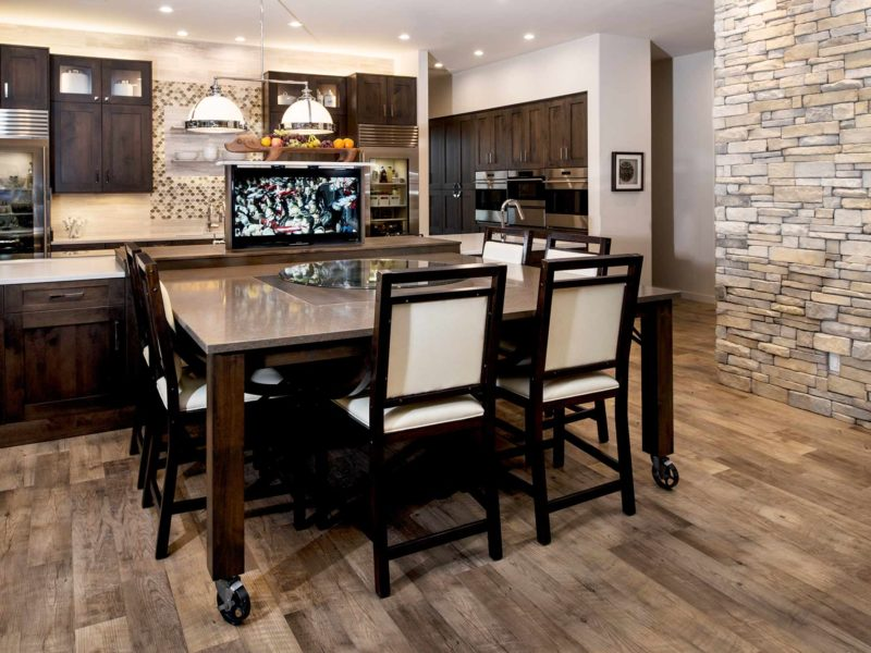 Modern south Tulsa kitchen with roll out table, pop-up television and large island, Caesarstone counter-tops, Sub-Zero Wolf appliances, brown cabinet storage and floating shelves