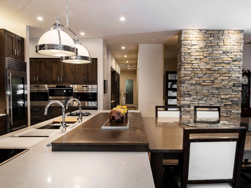 Modern south Tulsa kitchen with roll out wood table next to the large island with pop-up television Caesarstone quartz counter-top, lit stone wall and decorative pendant lights over the island