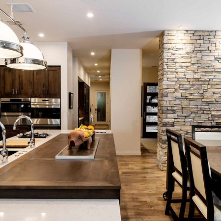 Modern south Tulsa kitchen with roll out wood table and large island with pop-up television, Caesarstone counter-top, stone wall, decorative pendant lights and Galley Workstation