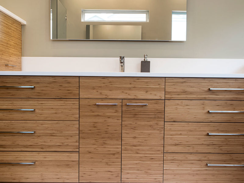 Modern Tulsa bathroom design and remodel with quartz counter and backsplash, medium brown wood grain cabinet storage, modern vanity mirror and slate gray tile flooring