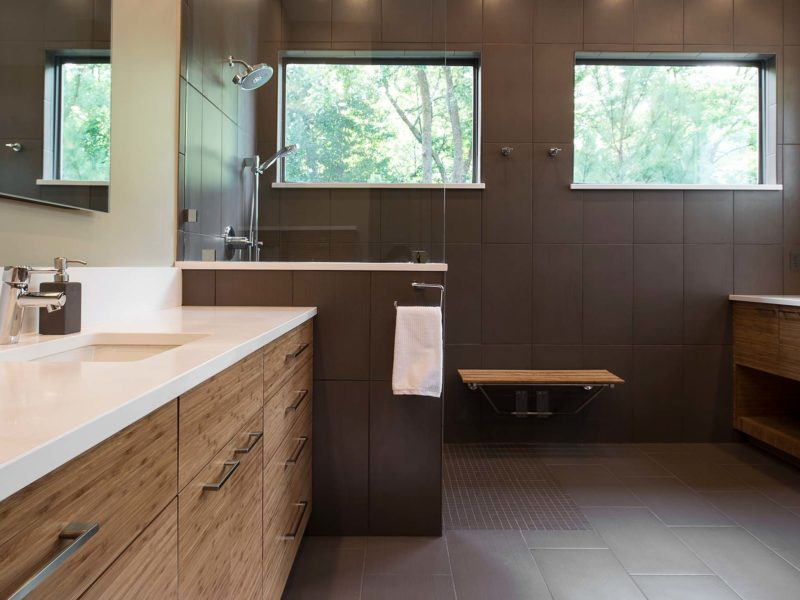 Modern Tulsa bathroom with large walk-in shower, slate gray tile walls, wood seating bench and brown cabinet vanity drawer storage