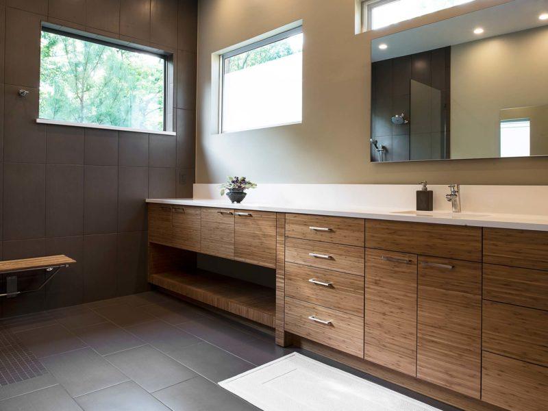 Modern Tulsa bathroom with quartz counter with backsplash, brown wood grain base cabinet storage and modern vanity mirror