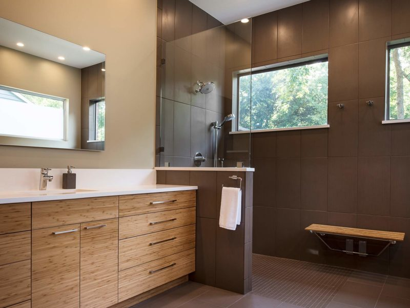 Modern Tulsa designed and remodeled master bathroom with medium brown wood grain base cabinet storage, walk-in shower glass partition, large wall tile and shower bench