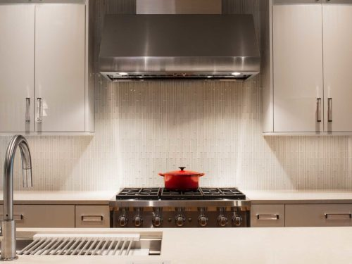 Tulsa kitchen design and remodel with stainless Wolf professional gas range and vent hood cooking space, ceramic tile backsplash and white cabinetry