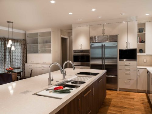 Modern Tulsa kitchen remodel island with rich brown wood cabinet storage, Galley Workstation kitchen sink, quartz counters, white cabinets, stainless Sub-Zero Wolf and Miele appliances and wood flooring
