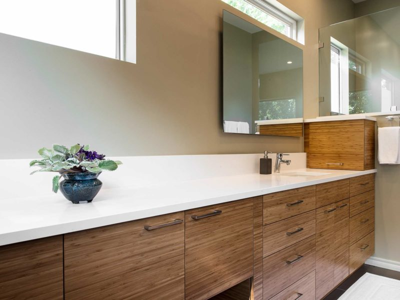Modern Tulsa master bath, quartz counter-top, backsplash, medium brown base cabinet drawer storage, large mirror, walk-in shower and glass partition