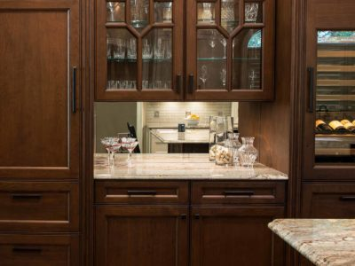 Old World Tulsa kitchen beverage center with tall Sub-Zero wine refrigerator, rich brown cabinetry, mirror backsplash and wood panel Sub-Zero freezer/refrigerator