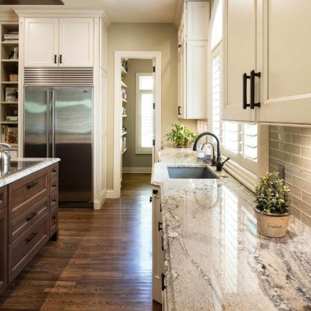 Old world Tulsa kitchen with large island featuring brown stained base cabinet storage, marble counter tops, subway tile backsplash and full size stainless freezer/refrigerator