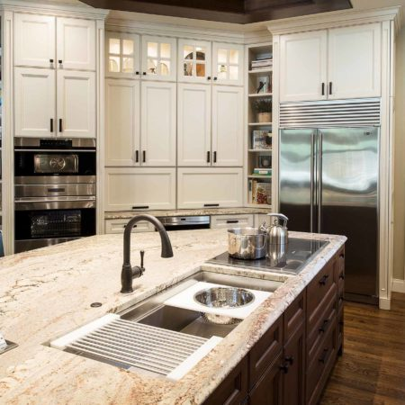Old world Tulsa kitchen with large island featuring a marble counter top, Galley Workstation with induction cooktop, stainless ovens, freezer/refrigerator and pantry storage