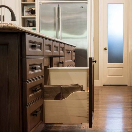 Old world Tulsa kitchen featuring rich brown island base storage, pull-out trash, beige base cabinet storage and refinished wood flooring