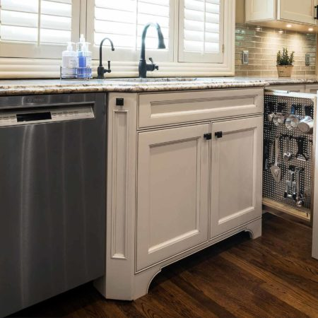 Old world Tulsa kitchen with stainless steel dishwasher, base pull-out storage and beige painted cabinets with Blanco clean-up sink backed by a subway tile backsplash