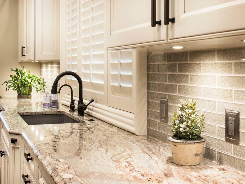 Old World Tulsa kitchen remodel with stainless steel dishwasher, beige cabinets, under cabinet LED puck lights, clean-up sink and subway tile ceramic tile backsplash