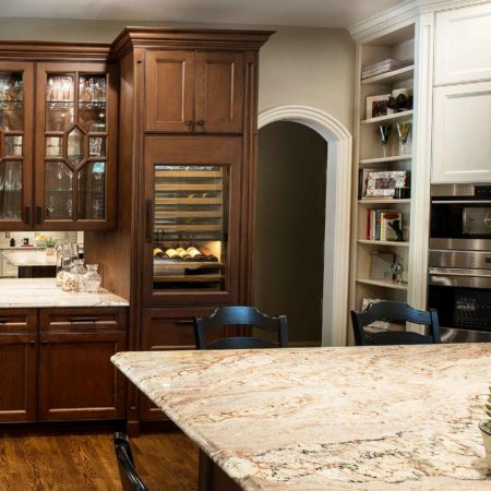 Old world Tulsa kitchen with beverage center, mirror backsplash and tall wine refrigeration in a rich brown cabinet finish, beige cabinets with stainless wall ovens and tall storage