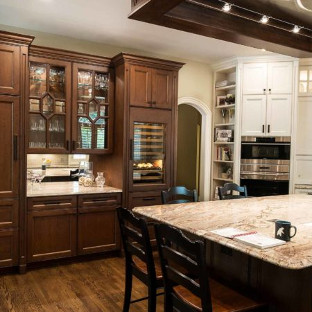 Old world Tulsa kitchen with wood flooring, large island with marble counter top, decorative ceiling vent hood, Galley Workstation, induction cooktop, beverage center with tall wine refrigerator, mirror backsplash, white tall cabinet storage and stainless appliances
