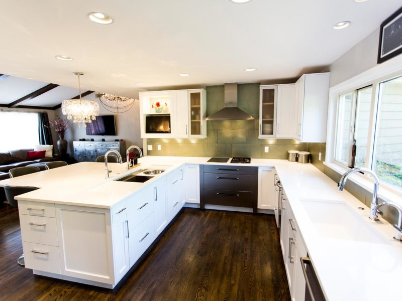 Open and functional trendy Tulsa kitchen with white cabinet, peninsula storage, Galley Workstation, Bosch stainless cooking appliances, glass tile backsplash, clean-up sink and Caesarstone white counters