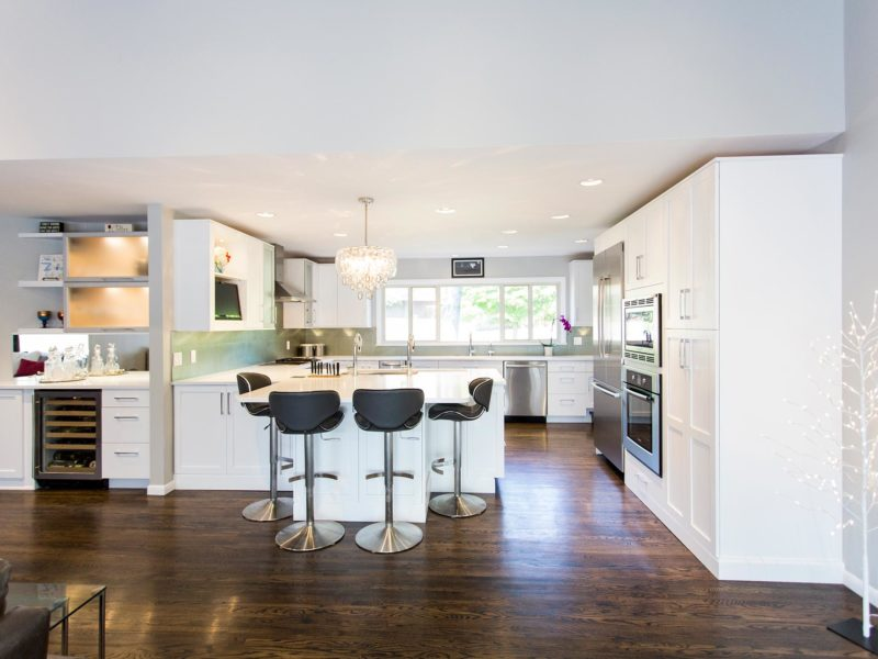 Open and functional trendy Tulsa kitchen design and remodel with white cabinets, bar space with wine refrigerator, frosted glass wall cabinets and decorative chandelier over the peninsula